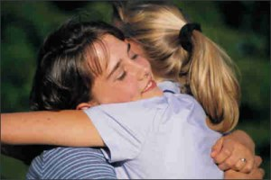 photo of two young women hugging and forgiving