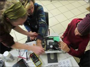 photo of three young people working on electronics together