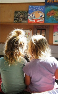 photo of two small girls sharing a book in a library