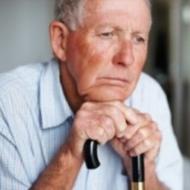 photo of seated, depressed, elderly man leaning on his cane handle with hands and chin