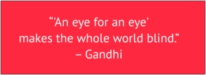"red box with white text: ""An eye for an eye only makes the whole world blind."" – Gandhi"