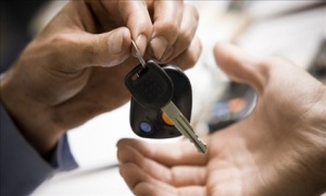 photo of one hand handing over a car key to another hand