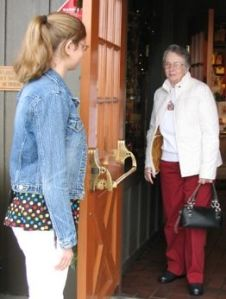 photo of 20-something woman holding door open for elderly woman