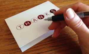 photo of thank-you card and hand with pen ready to write a thank-you note