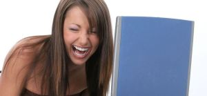 photo of young woman laughing hysterically while seated in front of her monitor