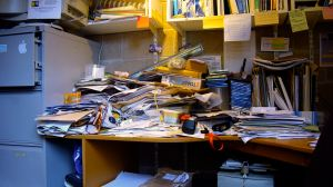 photo of basement office piled high with papers, files, books, etc.