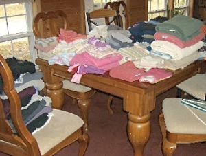 photo of folded laundry covering dining table and chairs