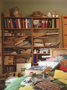 photo of bookshelf in bedroom with stacks and piles of books all over the bed, floor, and piled in messy piles on the bookshelf