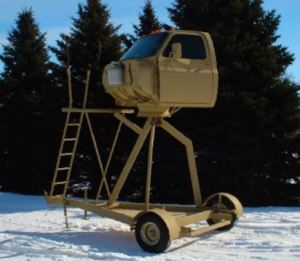 photo of pickup cab converted to an elevated deer hunting stand on wheels