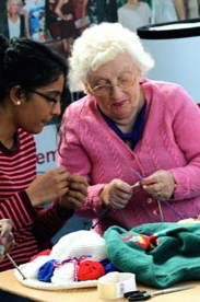 photo of senior woman teaching knitting to a younger woman