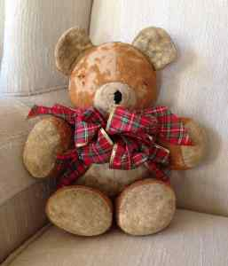 photo of worn teddy bear with large tartan bow