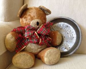 photo of worn Teddy with tartan bow and antique pie tin