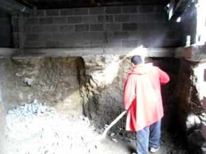 photo of man digging basement under existing house